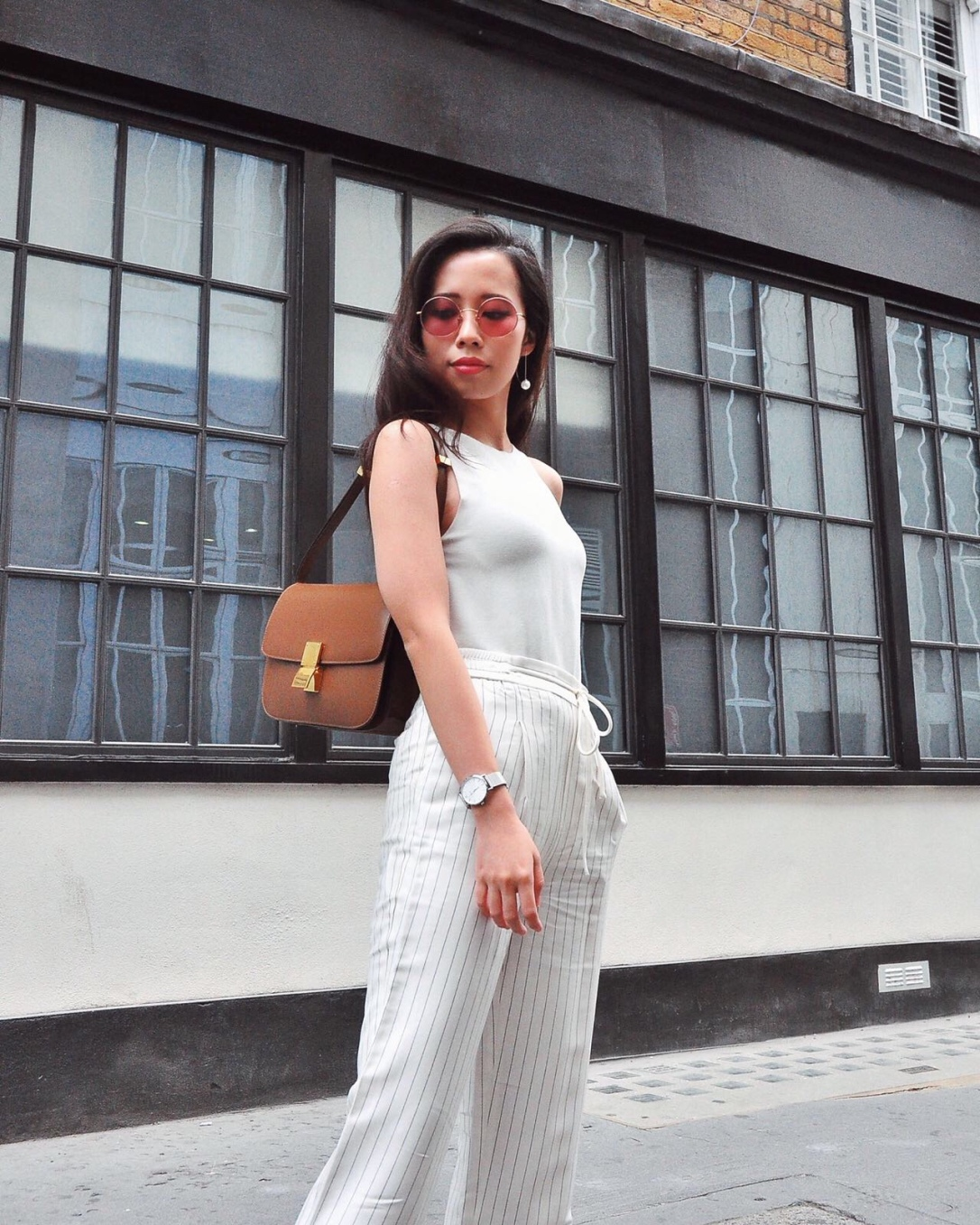 Wearing celine box bag from celine, white trousers, striped trousers, white sleeveless knit top, summer knit, brown celine bag, drawstring trousers, cluse watch, pearl earrings, pink rose tinted round sunglasses from jimmy fairly sunglasses